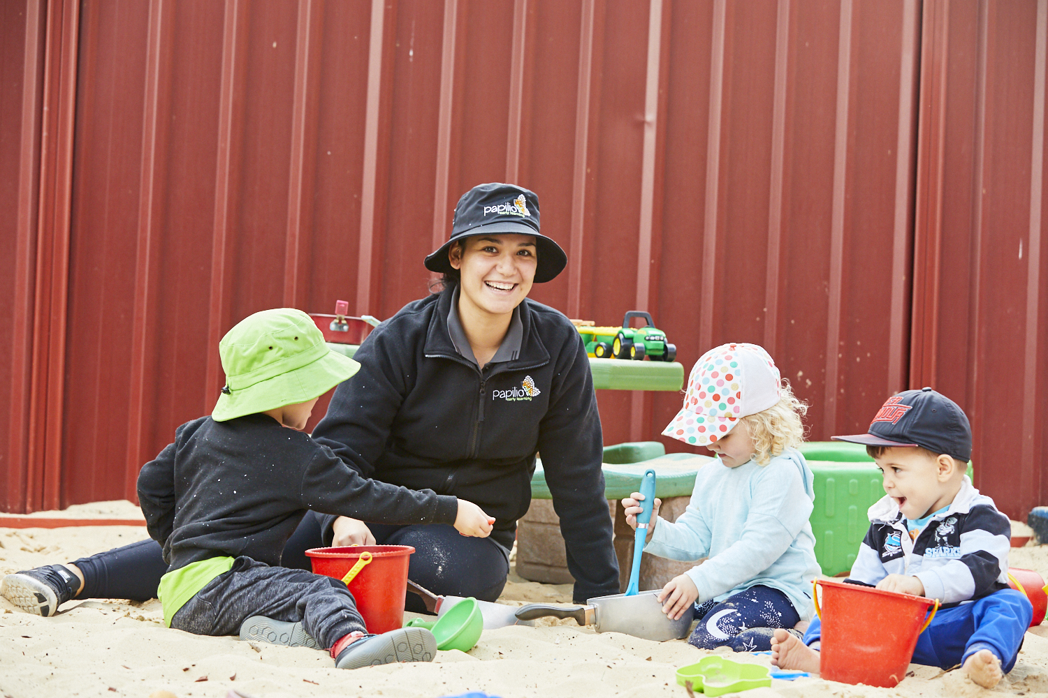 Child care educator with group of children playing in outdoor sand pit at Papilio Ingleburn